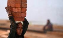 Mulher carrega tijolos emterreno que está sendo convertido em um centro de cuidados para coronavírus, em Nova Delhi (Taussef Mustafa/AFP)