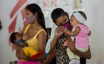 Deiglis, de 17 anos, espera com seu bebê por sua vez em uma clínica dos Médicos Sem Fronteiras em Vidoño, Venezuela, em 17 de março, para receber um implante hormonal que a protegerá de outra gravidez por cinco anos (AFP)