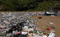 Coletor recolhe lixo plástico na Córsega, no Mar Mediterrâneo (Pascal Pochard-Casabianca/AFP)