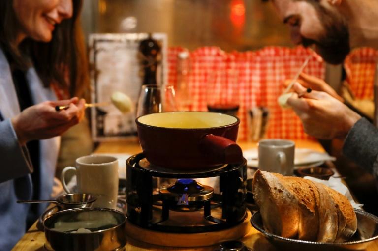 Um casal saboreia um fondue, o amado prato nacional suíço de queijo derretido com vinho branco em uma panela