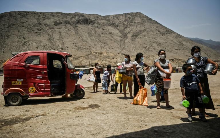 Peruanos aguardando em filas para receber alimentos, mantendo distância devido à pandemia de Covid-19, em Comas, ao norte de Lima, em 3 de fevereiro de 2021