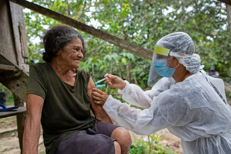 Maria Ferreira, 74, é vacinada contra a covid por um profissional de saúde com uma dose da Oxford/AstraZeneca, em uma comunidade às margens do Rio Negro, perto de Manaus, Amazonas, em 9 de fevereiro de 2021