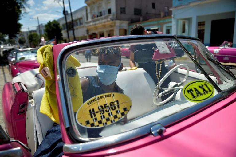 O motorista de um táxi particular limpa seu carro em Havana, em 19 de março de 2020