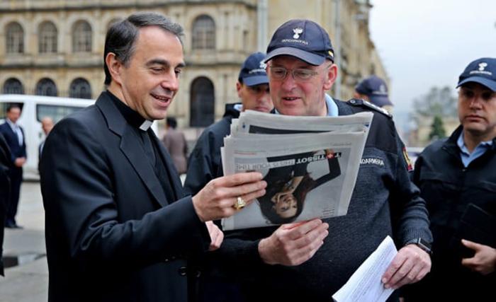 Dom Ettore Balestrero, então núncio apostólico na Colômbia, e Domenico Giani, principal guarda-costas do papa, leem um jornal enquanto caminham pelas ruas no centro de Bogotá em preparação para uma visita papal em maio de 2017