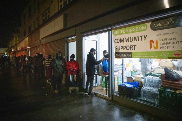 Estudantes estrangeiros fazem fila para pegar pacotes de ajuda alimentar no Newham Community Project, em Londres, em 16 de fevereiro de 2021