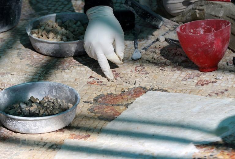 Um trabalhador restaura o piso de mosaico de uma antiga igreja bizantina na cidade jordaniana de Rihab, em 9 de fevereiro de 2021