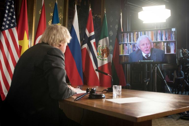 O primeiro-ministro britânico, Boris Johnson, assiste a mensagem em vídeo do naturalista britânico David Attenborough na abertura de uma sessão do Conselho de Segurança da ONU sobre o clima, em 23 de fevereiro de 2021