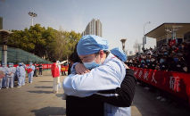 Médico (D) abraça assistente ao fim da força-tarefa montada em Wuhan, na China: alívio com o controle da expansão do vírus (STR / AFP)