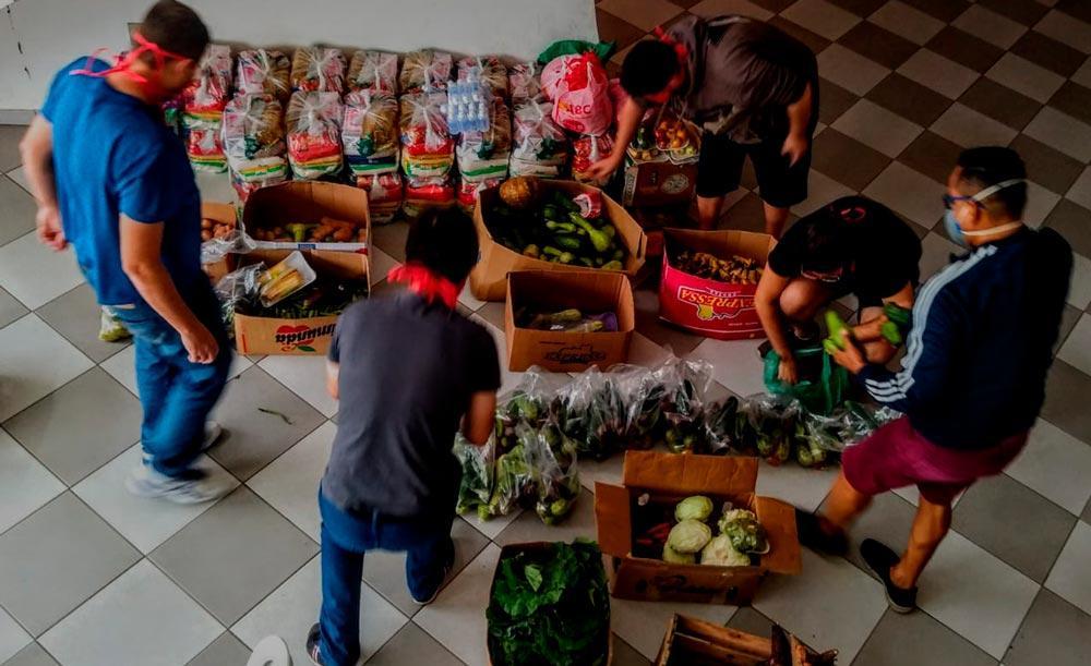 Voluntário organizam alimentos arrecadados para distribuição a famílias carentes: redes de ajuda perderam força