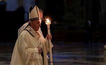 O Papa Francisco segura uma vela ao chegar para celebrar a Missa por ocasião da celebração do Dia Mundial da Vida Consagrada na Basílica de São Pedro no Vaticano em 2 de fevereiro de 2021. (Andrew Medichini/AFP)