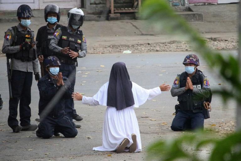 Imagem divulgada pelo Myitkyina News Journal mostra freira ajoelhada em frente à polícia para pedir que não disparem contra os manifestantes pró-democracia em Myitkyina, norte de Mianmar