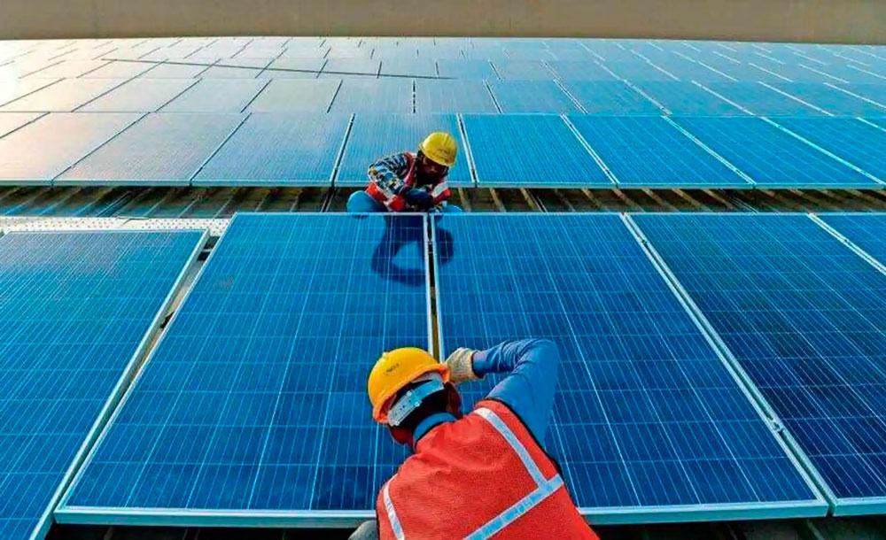 Trabalhadores indianos instalam painéis solares: benefícios de limitar as emissões