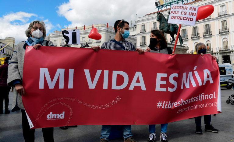 Um grupo de pessoas segura uma faixa em manifestação de apoio à lei que legaliza a eutanásia em Madri, Espanha