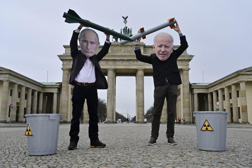 Ativistas com máscaras dos presidentes Putin (E) e Biden (D) posam com imitações de mísseis nucleares em frente ao Portão de Brandemburgo, Berlim, em 29 de janeiro de 2021, para pedir mais progresso no desarmamento nuclear