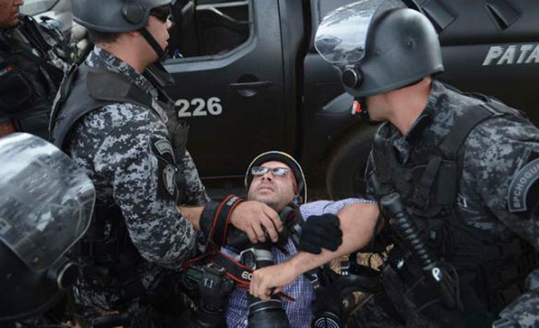 Repórter fotográfico da agência Reuters é conduzido pela polícia durante manifestação