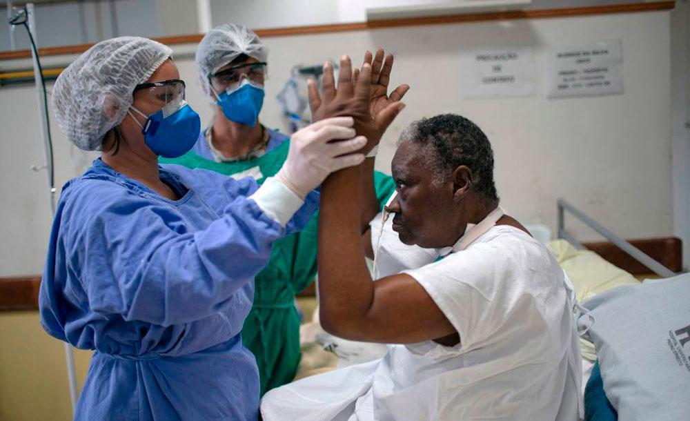 Enfermeiras ajudam paciente de Covid-19 em hospital do Rio de Janeiro