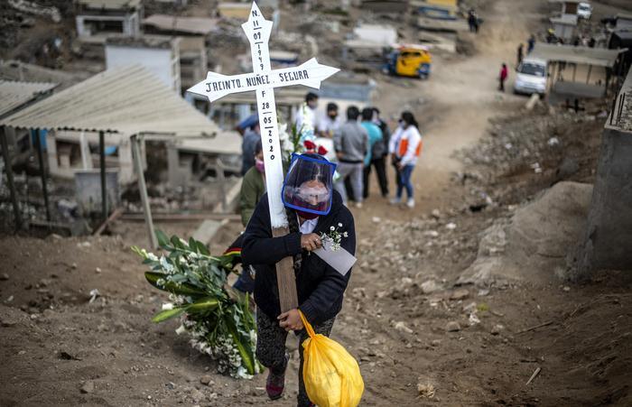 Parente de uma vítima da Covid-19 carregando uma cruz em cemitério de Lima, no Peru