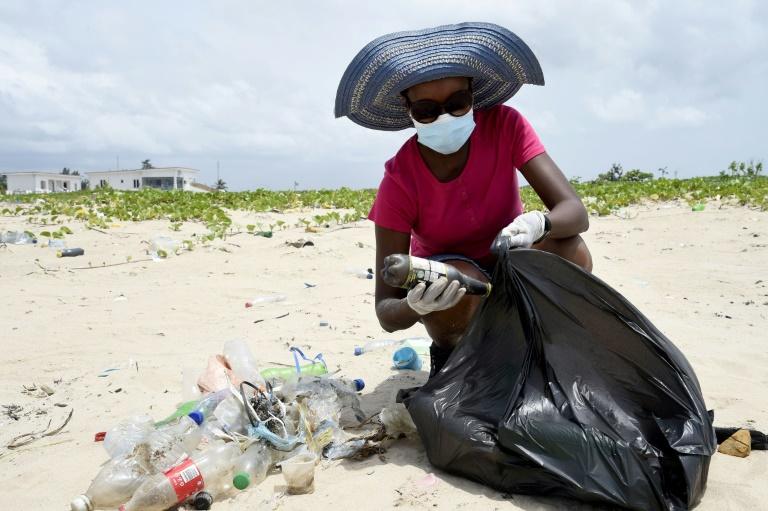 Voluntária junta resíduos plásticos na praia Lighthouse, de Lagos, sudoeste da Nigéria