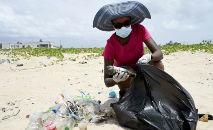 Voluntária junta resíduos plásticos na praia Lighthouse, de Lagos, sudoeste da Nigéria (Pius Uomi Ekpei/AFP)