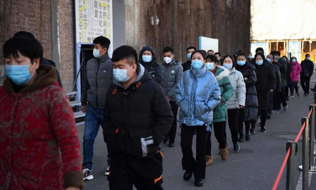 Pessoas formam fila em centro de vacinação contra a Covid-19 em Pequim, na China, nesta segunda-feira (4)