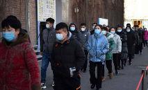 Pessoas formam fila em centro de vacinação contra a Covid-19 em Pequim, na China, nesta segunda-feira (4) (Greg Baker/AFP)