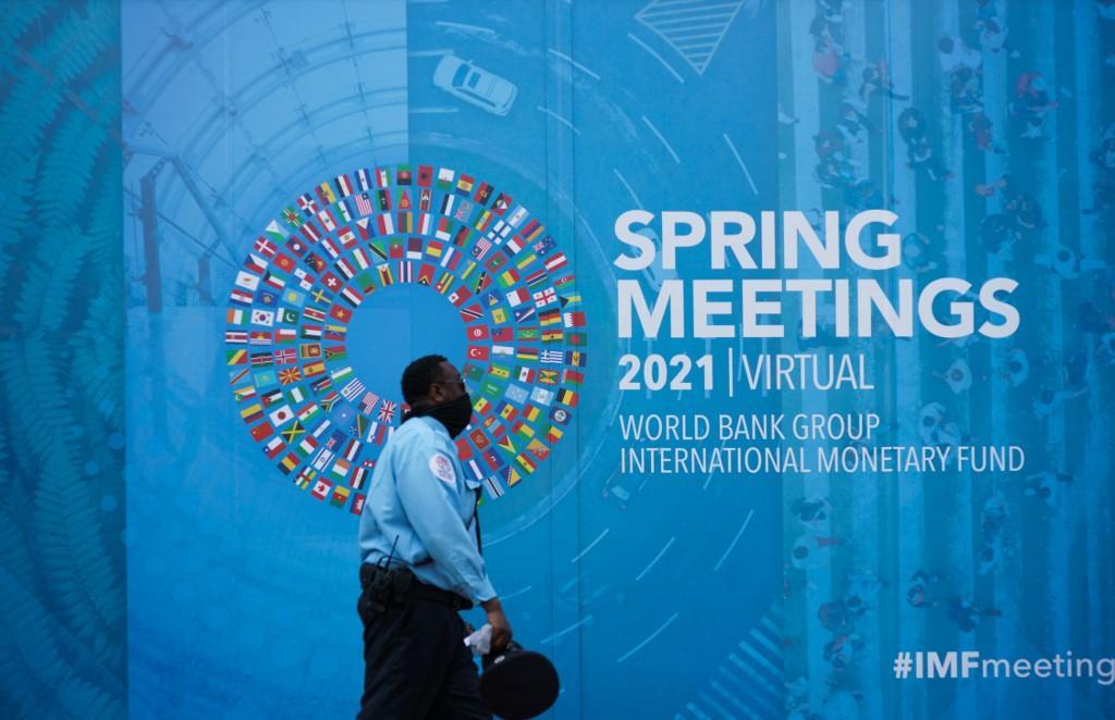 Pessoas passam por banner das Reuniões Virtuais da Primavera do Banco Mundial/Fundo Monetário Internacional em Washington, DC, em 7 de abril de 2021