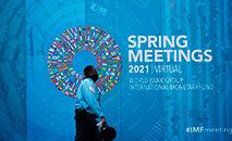 Pessoas passam por banner das Reuniões Virtuais da Primavera do Banco Mundial/Fundo Monetário Internacional em Washington, DC, em 7 de abril de 2021 (Mandel Ngan/AFP)