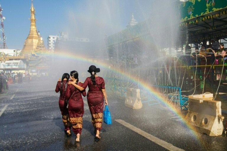 (Arquivo) Três mulheres caminham sob a água durante uma cerimônia do Ano Novo Budista, conhecido localmente como