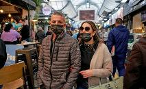 Israelenses caminham no mercado Mahane Yehuda, em Jerusalém, em 18 de março de 2021, usando as máscaras obrigatórias como parte dos esforços das autoridades para conter o coronavírus (Menahem Kahana/AFP)