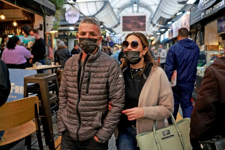 Israelenses caminham no mercado Mahane Yehuda, em Jerusalém, em 18 de março de 2021, usando as máscaras obrigatórias como parte dos esforços das autoridades para conter o coronavírus
