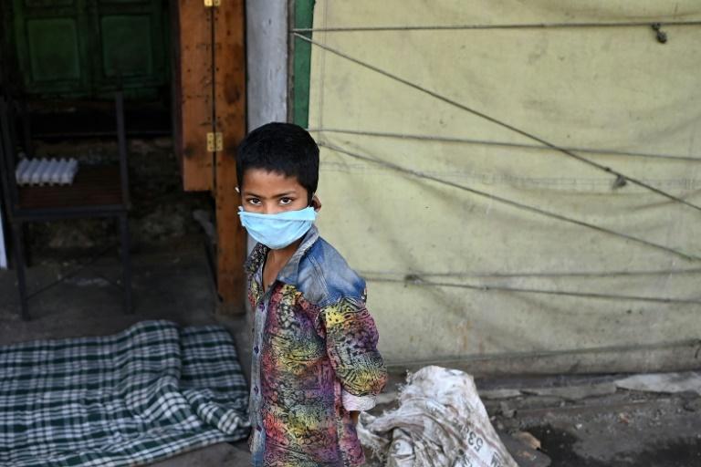 Menino passeia entre lojas fechadas pelas restrições impostas para conter a pandemia de coronavírus, em Nova Délhi, na Índia, em 17 de abril de 2021
