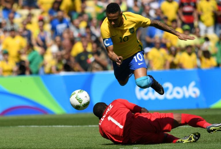 O atacante brasileiro Neymar salta sobre o goleiro hondurenho Luis López durante a semifinal de futebol masculino dos Jogos Olímpicos do Rio de Janeiro, em 17 de agosto de 2016 no estádio do Maracanã