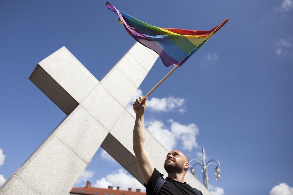Homem acena a bandeira do arco-íris durante a Primeira Parada Gay em Czestochowa, Polônia, em 8 de julho de 2018