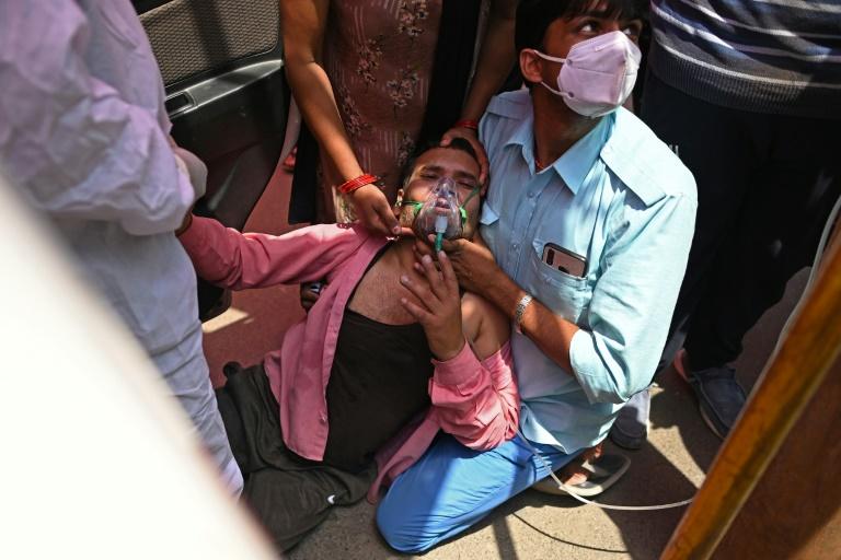 Paciente respira com a ajuda de oxigênio fornecido por um Gurdwara, um lugar de culto para os sijs,  em Ghaziabad, Índia