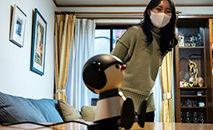 Nami Hamaura em sua casa em Tóquio com seu companheiro robô Charlie, 4 de fevereiro de 2021 (Philip FONG/AFP)