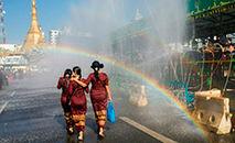 """(Arquivo) Três mulheres caminham sob a água durante uma cerimônia do Ano Novo Budista, conhecido localmente como """"Thingyan"""", em Yangon (./AFP)"""