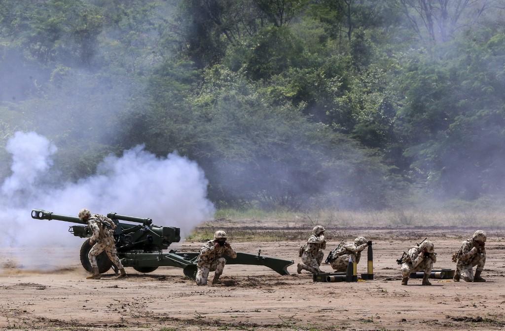 Soldados colombianos disparam um canhão durante exercícios militares em La Guajira, Colômbia, na fronteira com a Venezuela em 18 de abril de 2021
