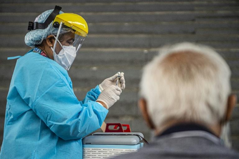 Profissional de saúde prepara uma dose da vacina Pfizer-BioNTech contra a Covid-19 para imunizar uma pessoa idosa, em um centro de vacinação em Lima, em 23 de abril de 2021