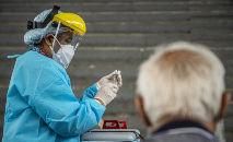 Profissional de saúde prepara uma dose da vacina Pfizer-BioNTech contra a Covid-19 para imunizar uma pessoa idosa, em um centro de vacinação em Lima, em 23 de abril de 2021 (Erenesto Benavides/AFP)