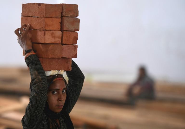 Mulher carrega tijolos emterreno que está sendo convertido em um centro de cuidados para coronavírus, em Nova Delhi