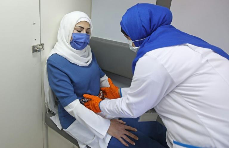 A parteira libanesa Heba Khoudary examina uma mulher em uma clínica móvel apoiada pelo Fundo de População das Nações Unidas (UNFPA) em Beirute em setembro de 2020