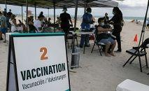 Cerca de 175 pessoas, muitos deles turistas latino-americanos, receberam a vacina da Johnson & Johnson neste domingo em um estande temporário na praia de South Beach, Flórida. (Eva Marie UZCATEGUI/AFP)