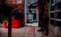 Moradora mostra rastro de sangue onde vítima foi morta em operação da PM (Mauro Pimentel/AFP)