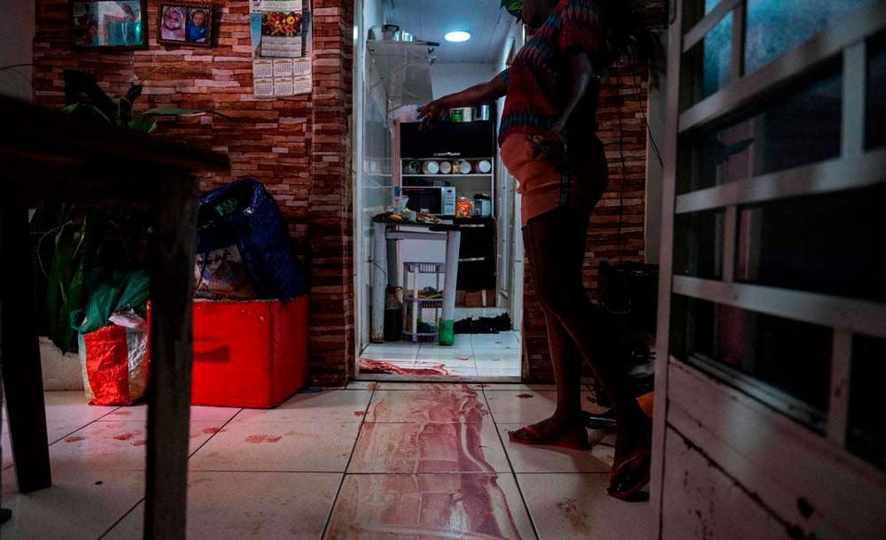 Moradora mostra rastro de sangue onde vítima foi morta em operação da PM