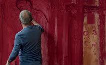 O artista pinta sobre vidro suas figuras deformadas (Pandora Filmes/Divulgação)