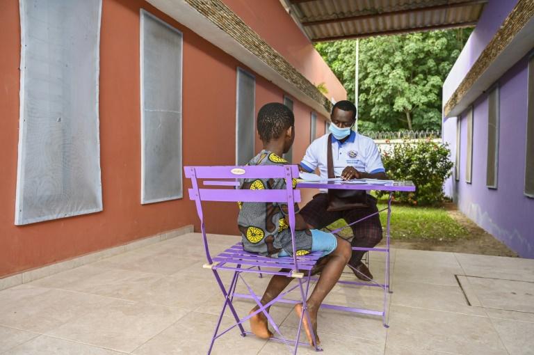 Trabalhador social escuta menino vítima de trabalho infantil no Centro para Crianças de Soubré, Costa do Marfim, em 6 de maio de 2021