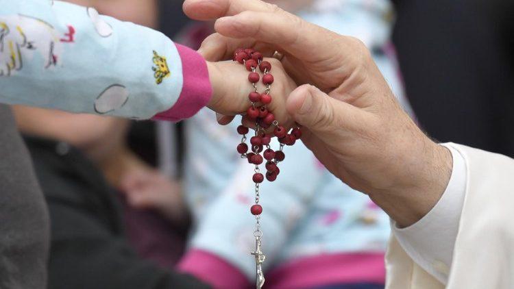 Papa Francisco toca a mão de criança com Terço na Praça São Pedro, na Audiência Geral de 26 de fevereiro de 2020