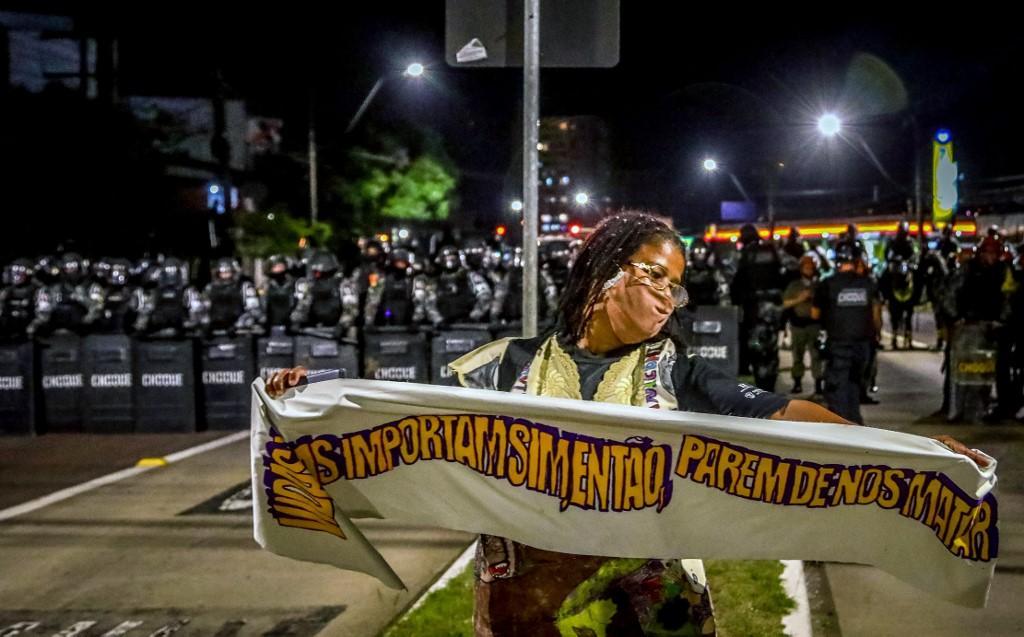 Uma mulher negra segura uma faixa em frente à tropa de choque durante um protesto contra a morte de João Alberto Silveira Freitas em Porto Alegre, Brasil, em 23 de novembro de 2020