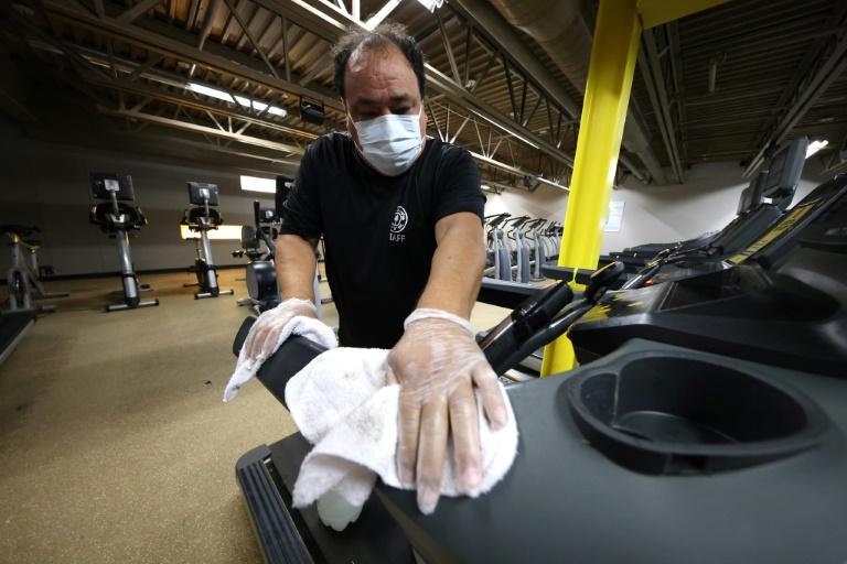 Funcionário limpa os equipamentos de uma academia em 24 de agosto de 2020 em Islip, Nova York