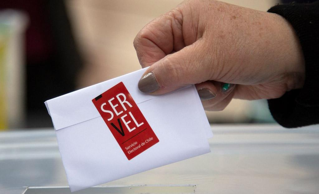 Funcionária mostra cédula selada para teste de uma urna em Santiago do Chile